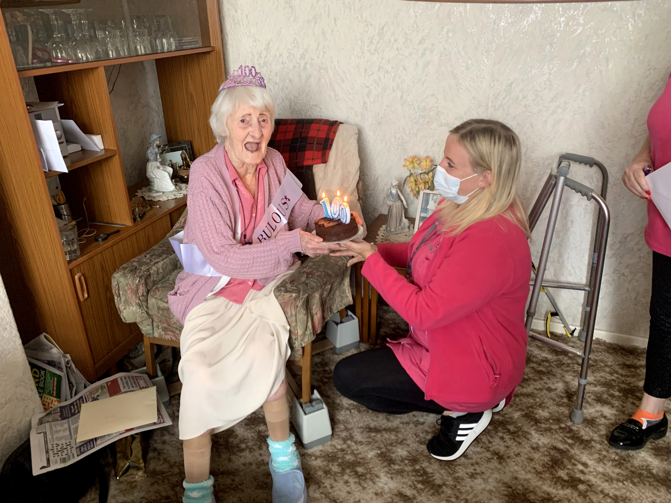 A carer from Alina Homecare presents Betty with her 100th birthday cake
